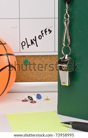 A silver whistle on a green notebook next to an orange basketball and a calendar with the date of the playoffs on it. - stock photo