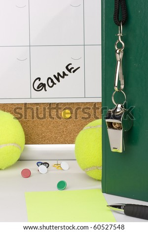 A silver whistle on a green notebook next to tennis balls and a calendar with the date of the game on it. - stock photo