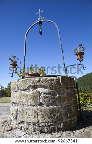 A simple and elegant stone well in a garden - stock photo