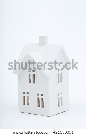 A simple, antique white porcelain house sitting on a white background. A delightful photo for a variety of ideas and concepts with plenty of room for text. Vertical, copy space. - stock photo