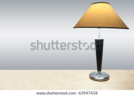 A simple lamp with yellow shade on a wooden desk. - stock photo