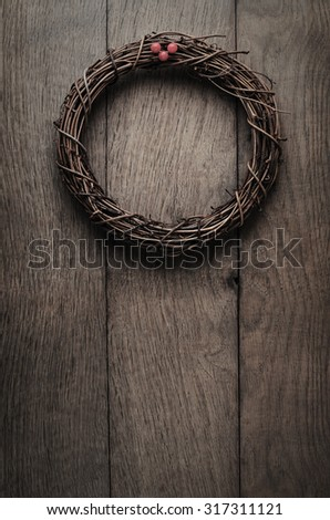 A simple, natural Christmas wreath woven from soft twigs with artificial red berries, hanging on an old, weathered oak wood plank door.  Low saturation and vignette to give vintage or retro effect. - stock photo
