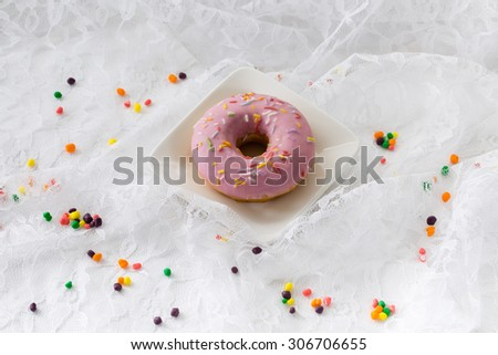 A simple, pink doughnut laying on a background of white lace. A dash of colorful sprinkles is gently placed among the lace. A great vertical format. - stock photo
