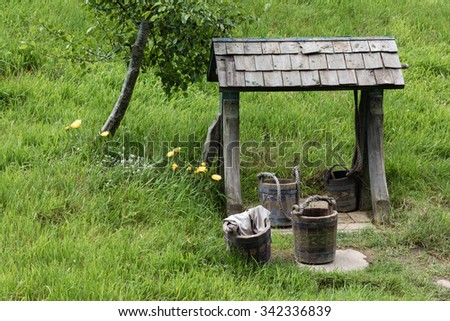 A simple, rustic well with wooden buckets and laundry. Taken on an overcast day, it reminds us of years gone by before our modern way of life. A nice horizontal format good for many ideas and concepts