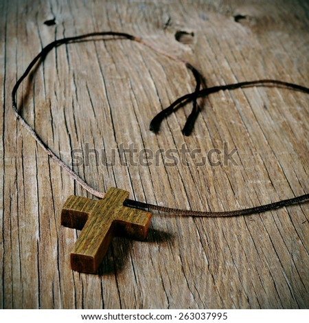 a simple wooden Christian cross on a rustic wooden surface - stock photo
