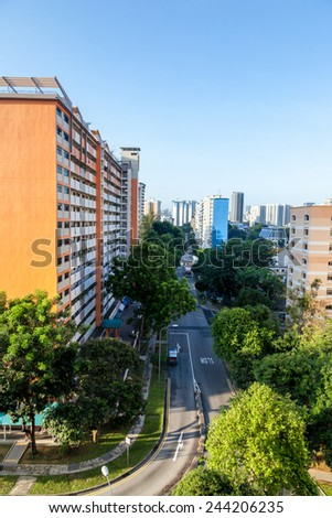 A Singapore residential housing estate with apartment blocks surrounded by trees against a clear blue sky. - stock photo