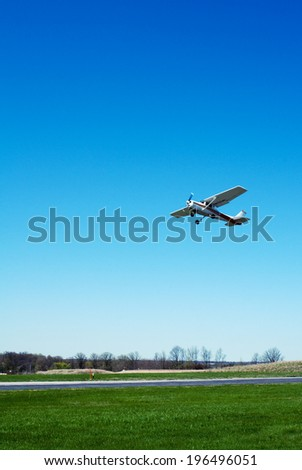A single airplane coming in to land on a runway. - stock photo