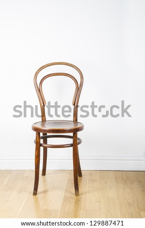 A single antique wooden chair, on a polished pine floor against a white wall - stock photo