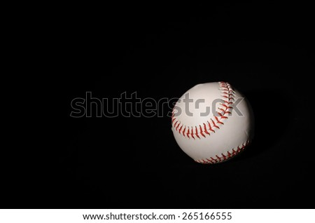 A single baseball on a black backdrop with single light illuminating it for isolation and drama. - stock photo