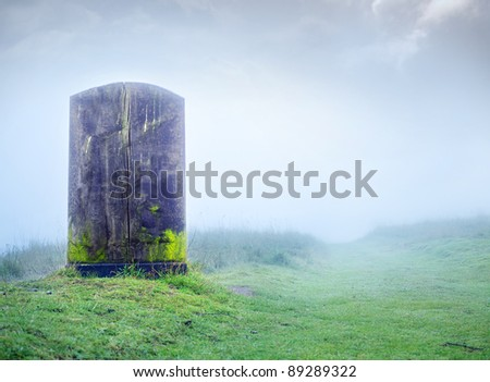 a single blank tombstone on a foggy hill