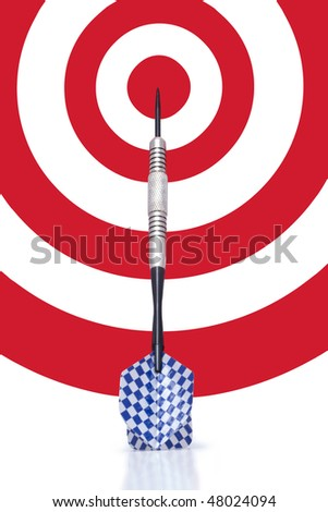 A single blue and white finned dart leaning against a red and white bull's-eye target.  Conceptual business image for being 'on target', 'moving forward', etc. - stock photo