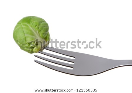 a single brussel sprout on a fork against white