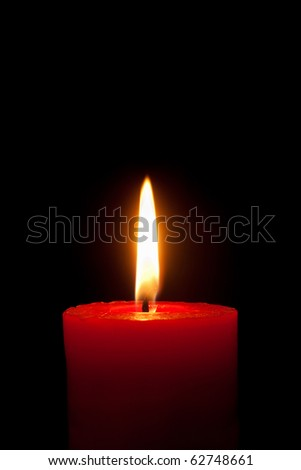 A single burning red candle isolated in front of black background - stock photo