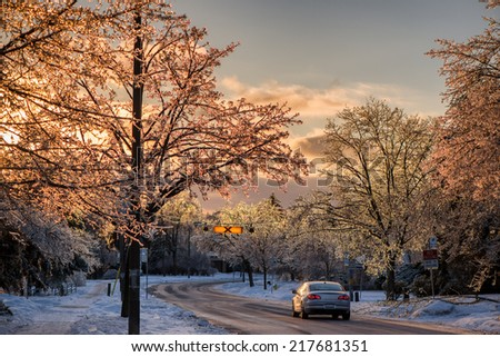 A single car is stopped on the road in an ice covered neighborhood after an ice storm.  The evening sun shines through the ice on the tree branches giving them a beautiful sparkling glow.    - stock photo