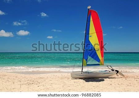 a single catamarran sits on an empty beach on a summer day - stock photo
