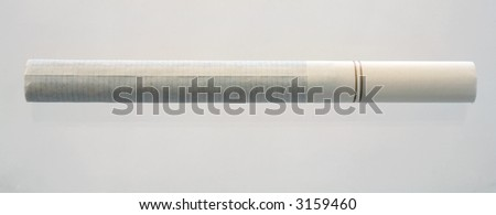 A single cigarette on a grey background.