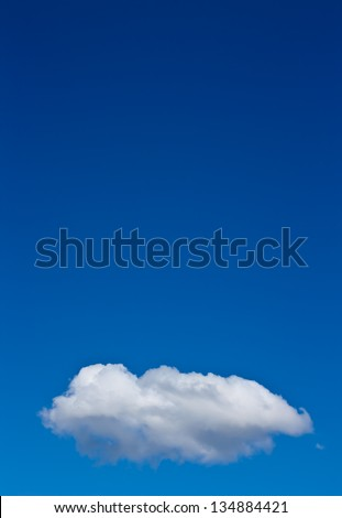 A single cloud in the lower part of the image with clear blue sky above. - stock photo
