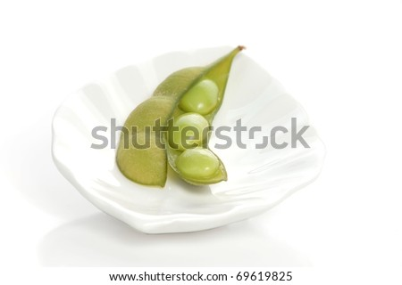 A Single Edamame Pod, Open to Expose the Soy Beans Inside, Sitting on a Beautiful, White Plate - stock photo