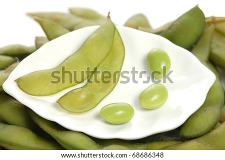 A Single, Empty Soy Bean Pod with Three Individual Soy Beans on a White Plate Sitting on a Bed of Soy Bean Pods - stock photo