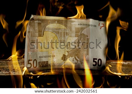 A single 50 euro money bill on a piece of wood just about to start burn. - stock photo