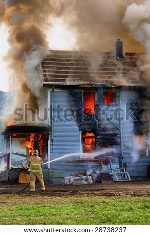 A single fireman fires his hose towards a burning house - stock photo
