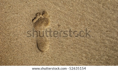 A single footprint in the sand from straight above - stock photo