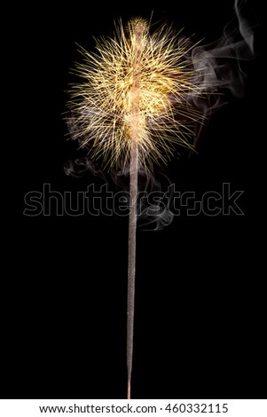 A single golden glowing sparkler isolated on a black background with some smoke around.