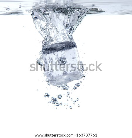 a single ice cube falls in the water before white background - stock photo