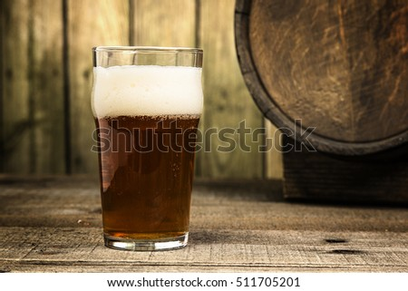 a single india pale lager style beer on a wood background with barrel