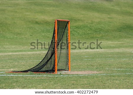 A single lacrosse goal on a turf field with a solid green background