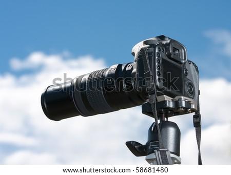 A single lens reflex camera mounted on a tripod. - stock photo