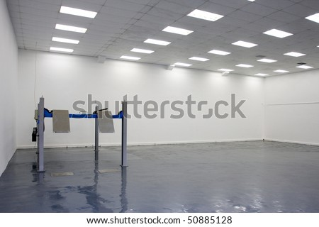 a single lift in car service garage with a blue floor (equipment for car diagnostics) - stock photo