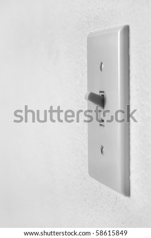 A single light switch on a white wall at an angle. - stock photo