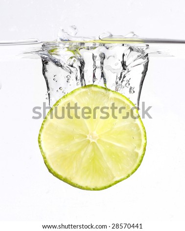 A single lime dropped with a splash into water - stock photo