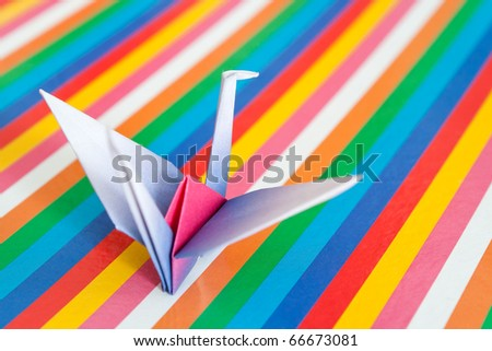 A single paper bird on a colorful stripes background. Shallow depth of field. - stock photo