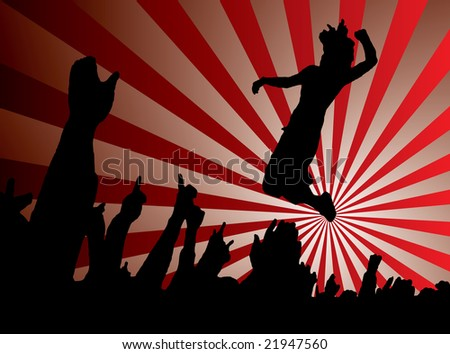 A single person jumping into a crowd at a concert with a sunset behind - stock photo