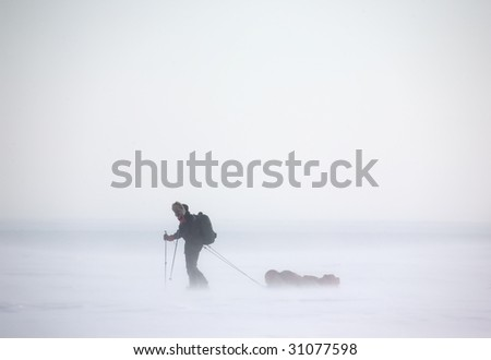 A single person on a winter expedition in a snow storm - stock photo