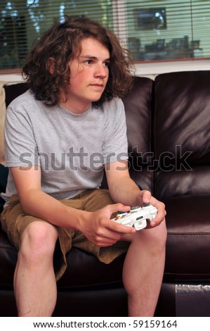 A single person sits on a couch and plays video games in his family room. - stock photo