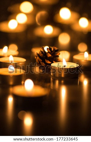 A single pine cone and a lot of tea candles - stock photo
