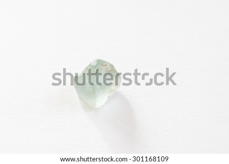 A single raw unpolished aquamarine gemstone. It is translucent with a light blue/cyan color - stock photo