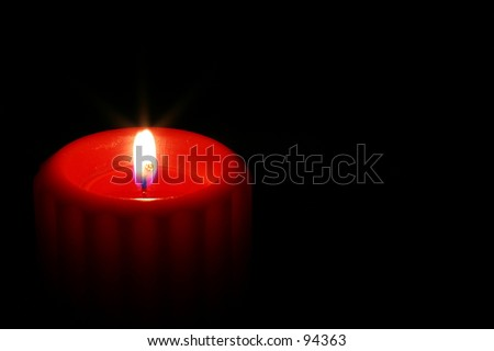 A single red candle burns alone in the dark.  There is a star on the flame. - stock photo