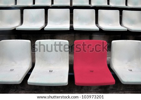 A single red chair in a multitude of white chair - stock photo