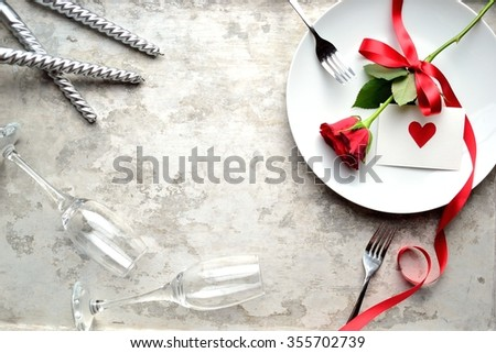 A single red rose with red heart message card on the white dish.Image of dinner on Valentines day - stock photo