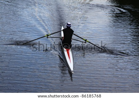 a single rower practices his rowing on the river - stock photo