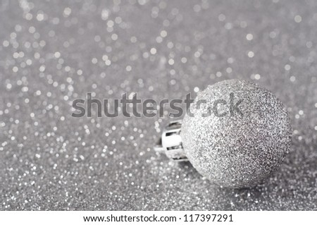 A single silver bauble, coated in glitter, resting on a silver glitter surface that softens into bokeh in the background. - stock photo