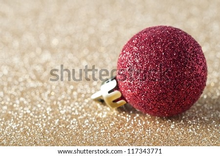 A single, sparkly red bauble, coated in glitter, resting on a gold glitter background that softens into soft focus bokeh in the background.  Copy space to left. - stock photo
