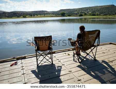 A single sportswoman sitting on a deck chair on a sunny, warm morning on a wooden fishing pier and fishing in a tranquil lake. An empty chair besides her shows she is with a partner. - stock photo