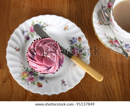 A single strawberry flavour cupcake with a cup of tea - stock photo