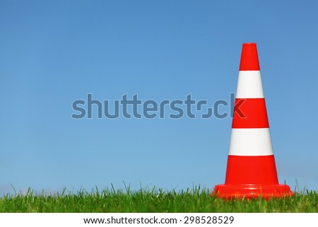 A single traffic cone on a green meadow - stock photo