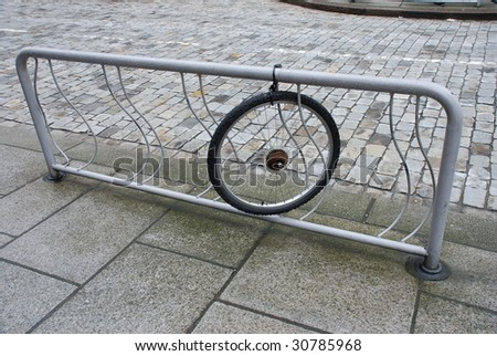 a single wheel in bycicle storage - stock photo